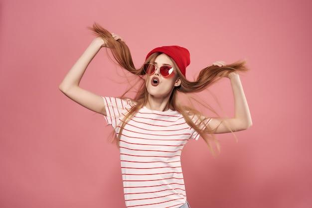 髪のモダンなスタイルのピンクの背景を保持しているかわいいファッションの女性