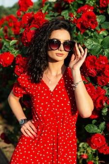 Симпатичная модная женщина с винтажными солнцезащитными очками и ювелирным браслетом в красном платье позирует возле куста с цветами роз в солнечном свете