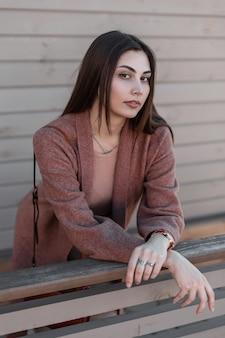 세련된 코트에 갈색 머리를 가진 섹시한 입술로 아름다운 눈을 가진 꽤 유행 매력적인 젊은 여자는 빈티지 나무 난간 근처에 서있는 레저를 즐깁니다. 여성스러운 사랑스러운 여자 모델 야외.