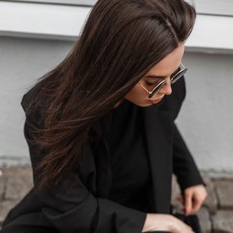 Довольно модная крутая молодая женщина в модной черной одежде в стильных солнцезащитных очках сидит на каменной дороге и смотрит вниз на открытом воздухе. портрет привлекательной современной девушки. модная одежда для женщин. повседневный стиль.