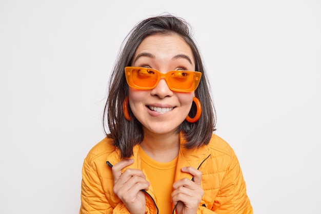 Pretty fashionable dark haired asian woman bites lips looks away wears orange sunglasses earrings jacket going to have walk during sunny spring day isolated over white wall. people style