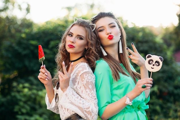 Pretty and fashionable girlfriends holding candies on stick.