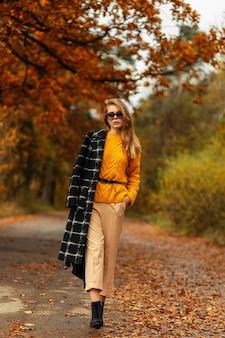 재킷, 니트 스웨터, 바지, 부츠를 신은 세련된 가을 옷을 입은 꽤 세련된 모델 여성은 화려한 단풍으로 공원을 산책합니다.