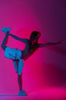 アートのカラフルな光で屋内で踊るトレンディな白い靴でスタイリッシュな服を着たかなりファッショナブルなモデルの若い女性。スポーティな女の子は、明るいネオンの驚くべき青い色のスタジオで片足で立っています。