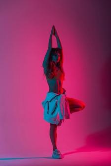 アートのカラフルな光で屋内で踊るトレンディな白い靴でスタイリッシュな服を着たかなりファッショナブルなモデルの若い女性。明るいネオンの驚くべきピンク色のスタジオで片足で立つスポーティな女の子