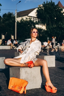 Pretty fashionable woman posing outdoor on the street