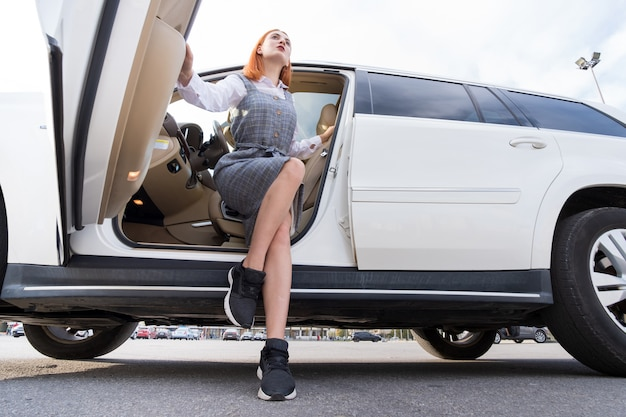 Pretty fashionable young woman driver in casual dress and sneakers sitting in expensive new car.