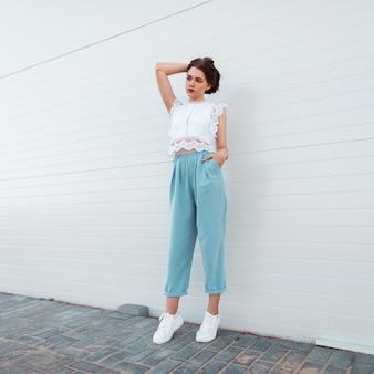 흰색 가죽 유행 운동화에 세련된 여름 옷에 꽤 유행 젊은 여자 모델 스탠드와 머리카락을 곧게 만듭니다