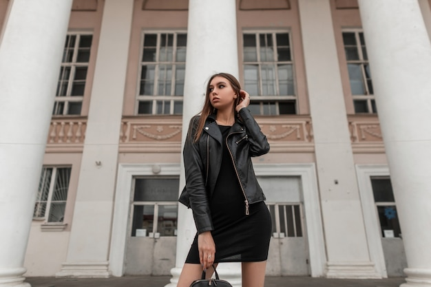Pretty fashionable young woman in a trendy black leather jacket in an elegant dress with a stylish bag stands near a vintage white columns on the street. modern european girl. autumn casual fashion.