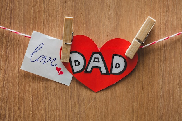 Pretty father's day composition with notes and clothes pegs