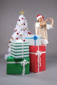 Красивая женщина вокруг рождественских подарков на сером