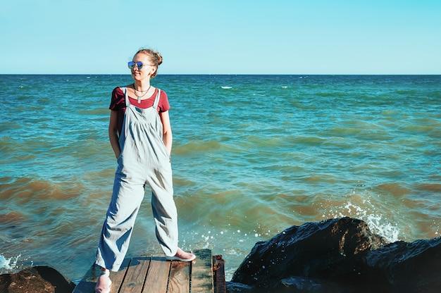 Pretty female in blue sunglasses on beach
