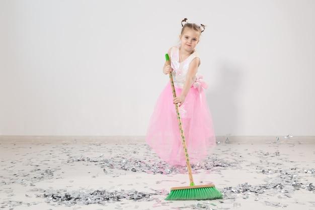 クリスマスパーティーの後にアパートを掃除するきれいな女性の子供。