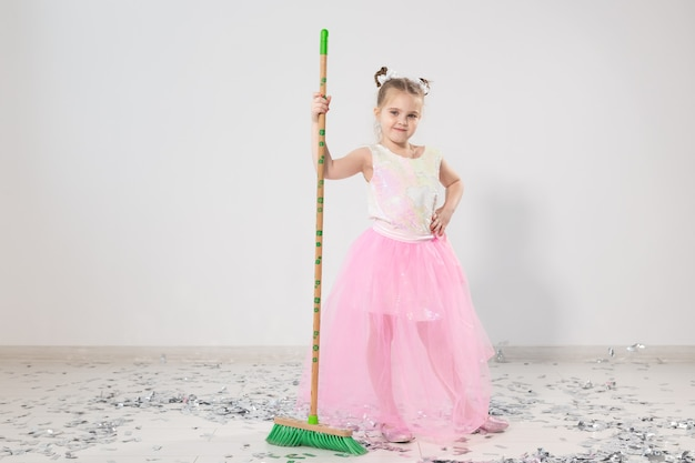 Pretty female child cleaning apartment after christmas party.