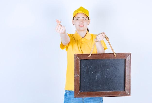 Красивая женщина-курьер делает денежный знак, держа рамку в левой руке перед белой стеной