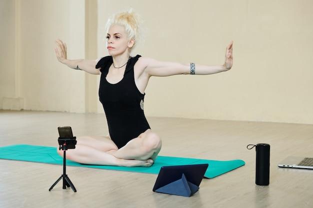 Симпатичная танцовщица делает упражнения для спины и рук, снимая себя во время тренировки для социальных сетей