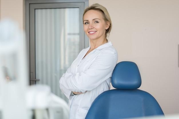 Милая женщина стоматолог позирует в клинике