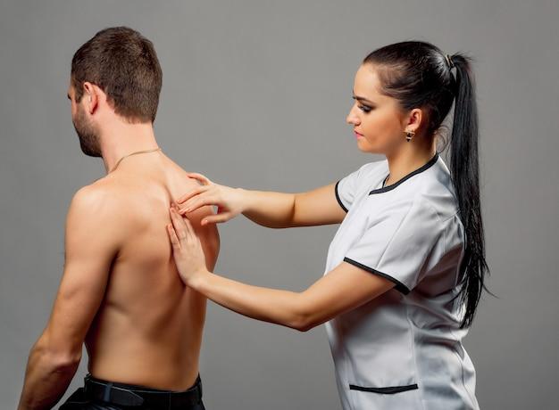 Pretty female doctor examining back of man on grey