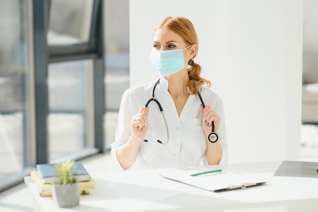 病院で保護マスクのきれいな女性医師