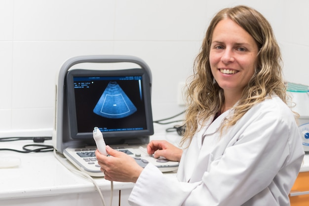 Pretty female doctor, posing while is doing a sonography.