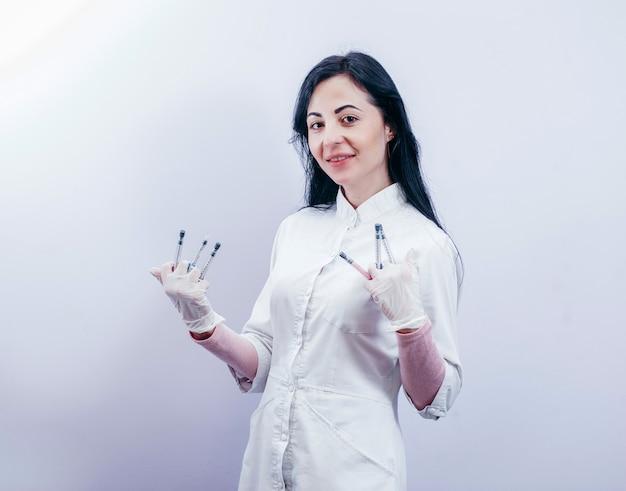 흰색 의료 가운을 입고 회색 공간에서 주사기를 들고 예쁜 여성 의사