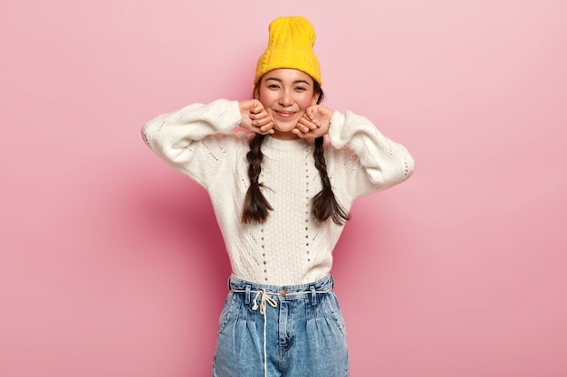 Pretty female dressed in fashionable yellow hat, white sweater and jeans, has enthusiastic and charming look in camera, glad expression, isolated over pink wall