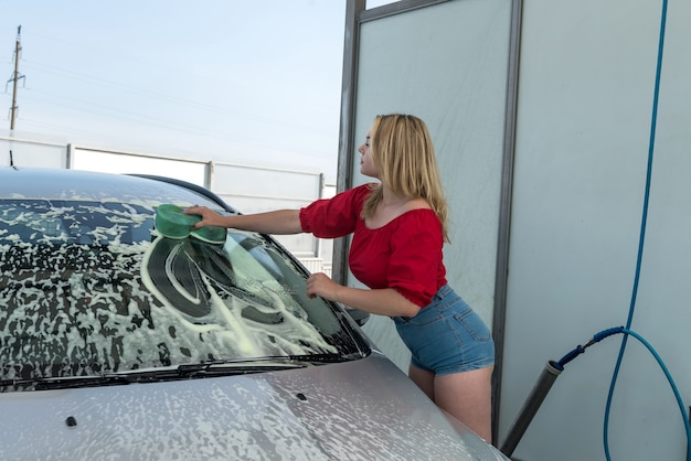 Pretty female driver with green sponge in white foam washing modern auto. manual car washing service.
