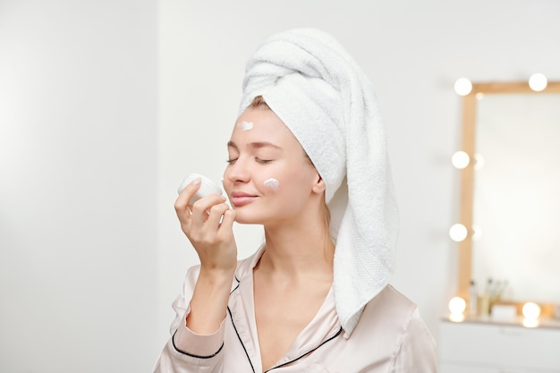 朝のシャワーの後、顔に塗っている間、新しいフェイシャルクリームの香りを楽しんでいるきれいな女性