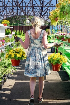 Pretty female florist works with flowers in a garden center.
