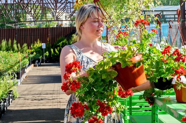 예쁜 여성 꽃집은 정원 센터에서 꽃으로 일합니다.