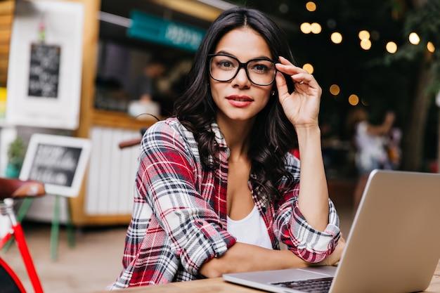 예쁜 여성 프리랜서는 흐림 도시에 포즈를 취하는 유행 안경을 착용합니다. 좋은 하루에 노트북을 사용하는 우아한 검은 머리 소녀.
