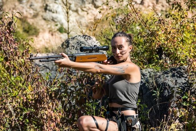 야생의 자연에서 무기와 숲에서 상단에 예쁜 여성 사냥꾼. 생활 양식