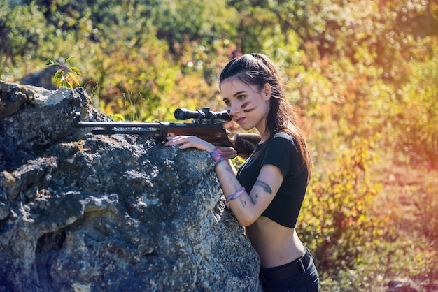 Pretty female hunter in top in forest with weapon in wild nature. lifestyle