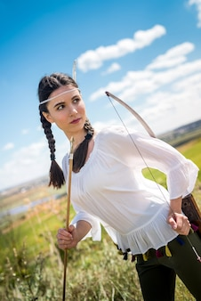 弓を持ったきれいな女性ハンターが屋外でネイティブアメリカンインディアンとして遊ぶ