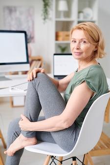 Красивая женщина в спортивной одежде с повязками под глазами на лице, сидя на стуле перед камерой в домашней обстановке