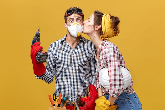 Симпатичная женщина целует мужа в щеку, благодарна ему за ремонт ее гардероба. удивленный рабочий в маске, держащий сверлильный станок, рад получить поцелуй от своей девушки