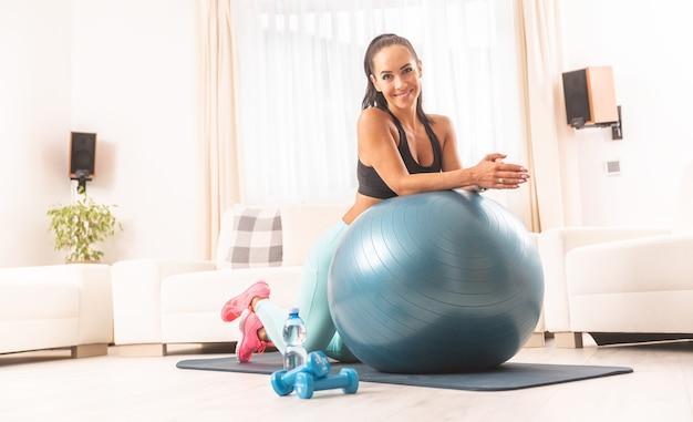 Симпатичная женщина опирается обоими локтями на мяч, готовый к тренировке в своей квартире.