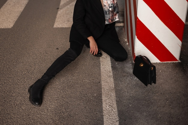 Pretty female legs in fashion black jeans with bag on asphalt