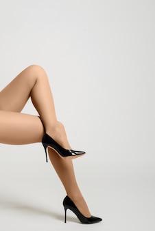 白い背景の上の黒いハイヒールときれいな女性の脚