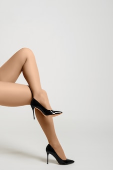 Pretty female legs with black high heels on white background