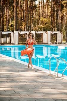 A pretty female lifeguard running near the pool