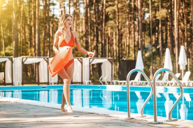 A pretty female lifeguard walking near the pool