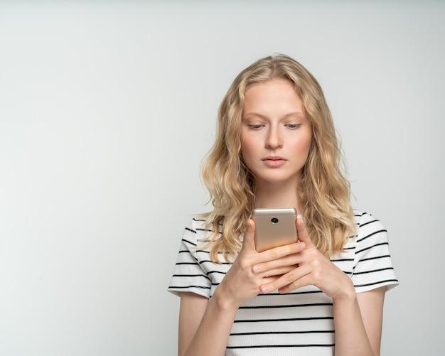 예쁜 여성 흰 벽, 회색 배경 근처에 서있는 휴대 전화에 소셜 미디어를 찾고.