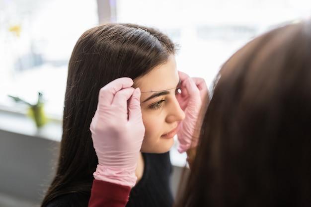 白い手袋のきれいな女性のマスターが若いモデルの眉の輪郭を決定します