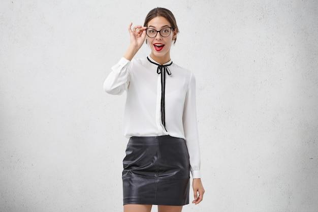 きれいな女性モデルはエレガントな白いブラウスと革の黒いシャツを着ています
