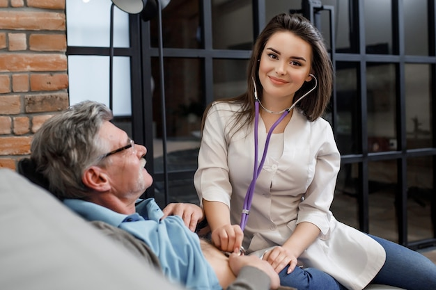 年配の男性の心臓の鼓動を聞きながら聴診器を持っているきれいな女性の民間医師。