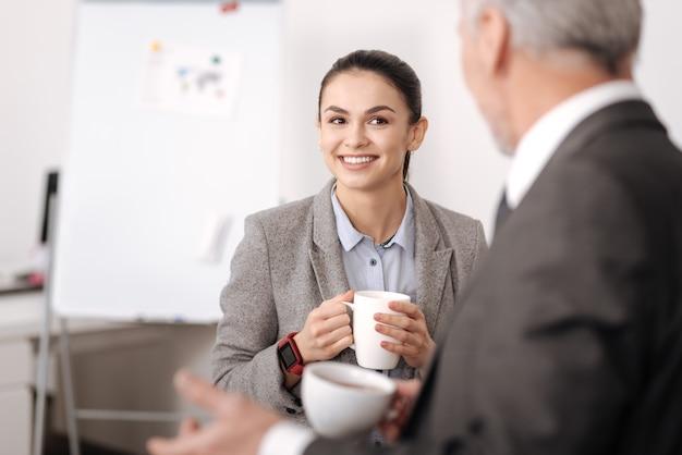 朝のお茶を飲みに行く間彼女の同僚を見ている彼女の眉を上げるきれいな女性