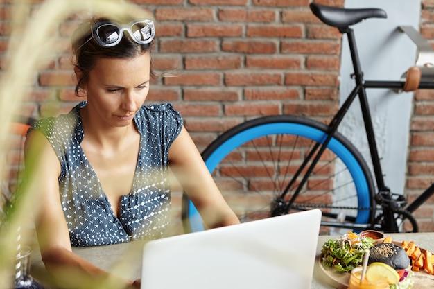Симпатичная женщина читает новости во время серфинга в интернете на портативном компьютере, глядя на экран с сосредоточенным выражением лица