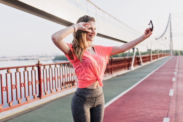 Pretty female runner using smartphone for selfie at cinder track. sensual girl in sport clothes taking picture of herself.