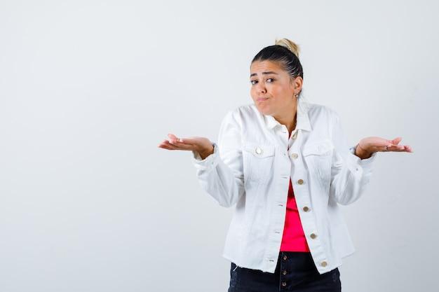 白いジャケットで無力なジェスチャーを示し、混乱しているように見えるきれいな女性。正面図。